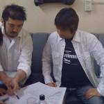 楽屋で打合せ中の河崎真澄さん(右)。左はキーボードの沢水友彦君。